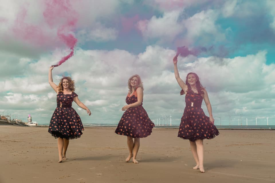 Image of three women in 50s fit and flare dresses holding up pink smoke flare on Redcar beach.